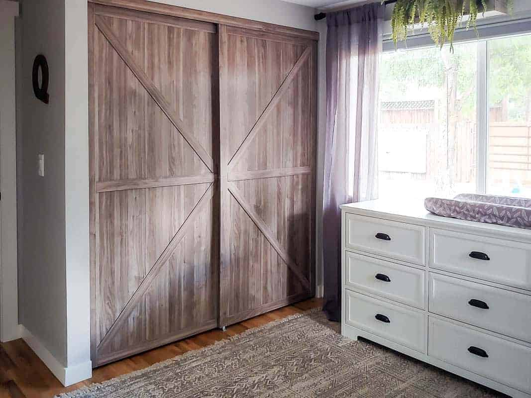 Barn closet doors and white dresser for the baby nursery room