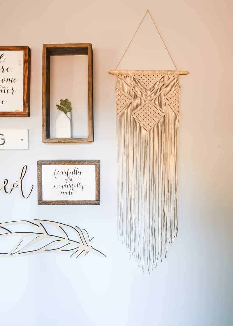Macrame hanging wall decor on the edge of nursery gallery wall art with rustic wood signs