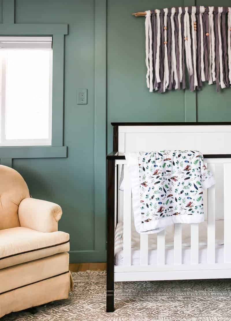 White crib with black trim in front of a green board and batten accent wall with tan rocker sitting next to crib under the window with in vintage style rug on floor and yarn wall hanging as wall decor