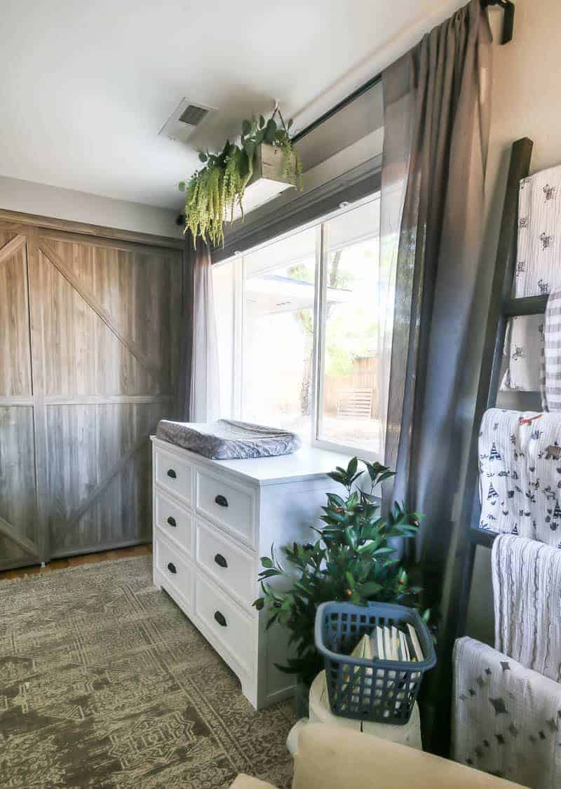 Barn door closet doors in background with white dresser shown under window with gray curtains and DIY blanket ladder and book basket sitting in the foreground of this baby girl nursery