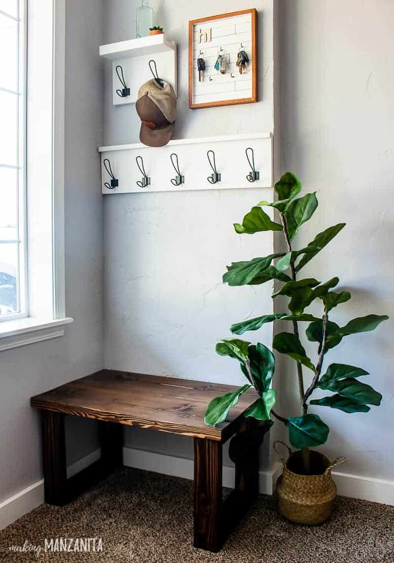 Small entryway showing the racks, DIY key holder, small entryway bench and an indoor plant.