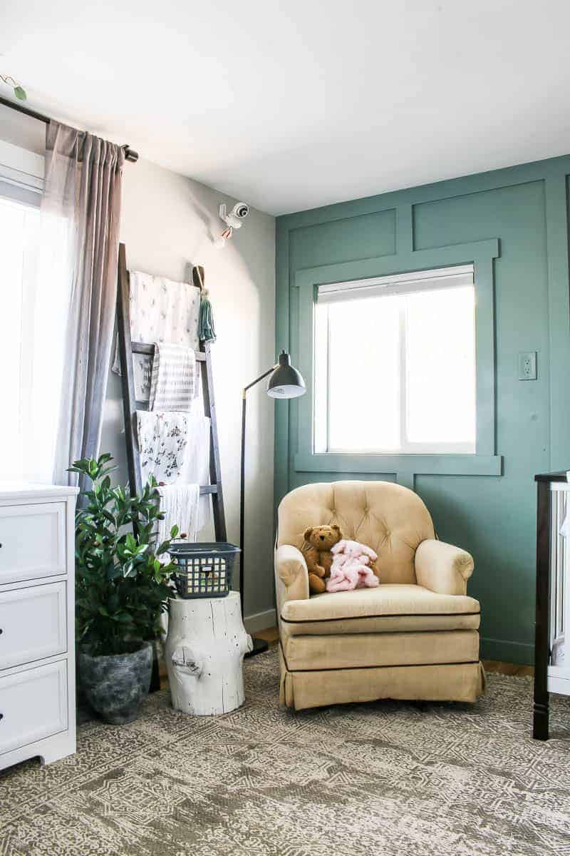 Blanket ladder in corner of nursery with baby blankets, window with gray curtains, faux olive tree on ground with book basket sitting on white painted stump next to a tan rocker with a vintage style area rug