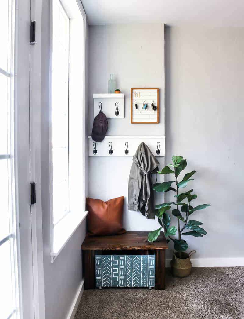 Full image of the entryway decor showing coat racks, key holder, leather pillow, indoor plant, wooden bench and wooden shoe storage