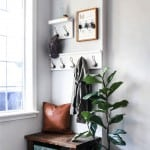 Entryway design which includes coat racks, key holder, leather pillow, wooden bench, wooden shoe storage and indoor plant with text overlay that says Small Entryway