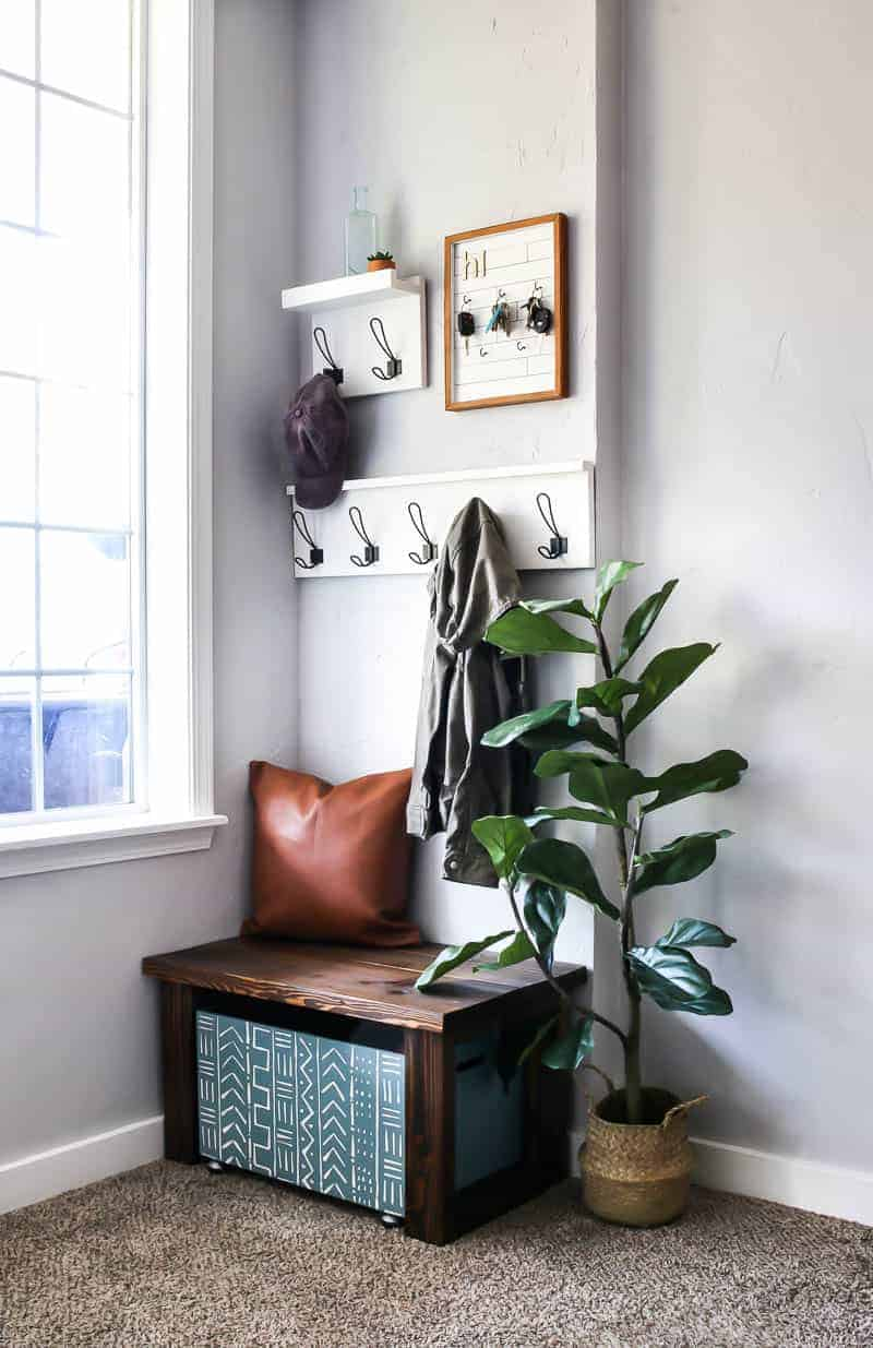 Farmhouse leather throw pillow on the wooden bench and wooden storage, indoor plant, coat racks on the wall and key holder for the entryway design