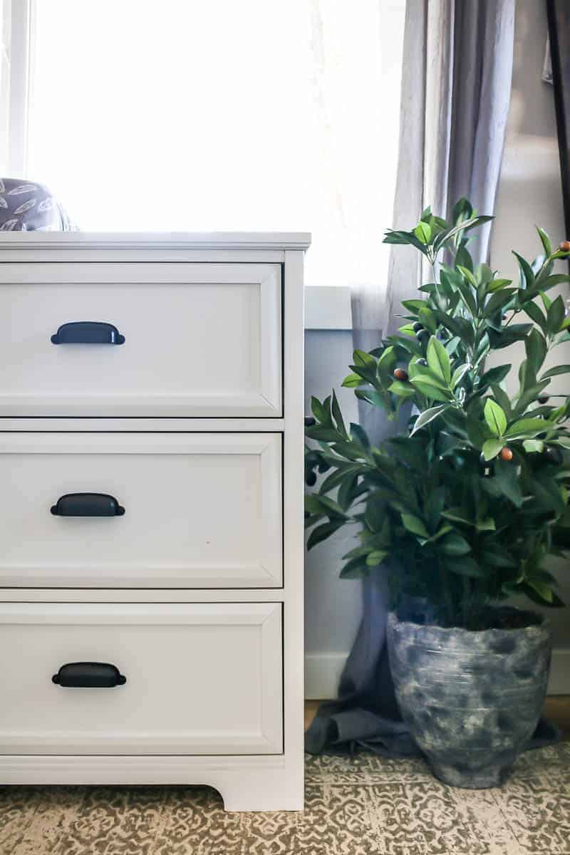 Zoomed in photograph of the front side of a white dresser with black cup pulls hardware with faux olive tree sitting on ground next to it