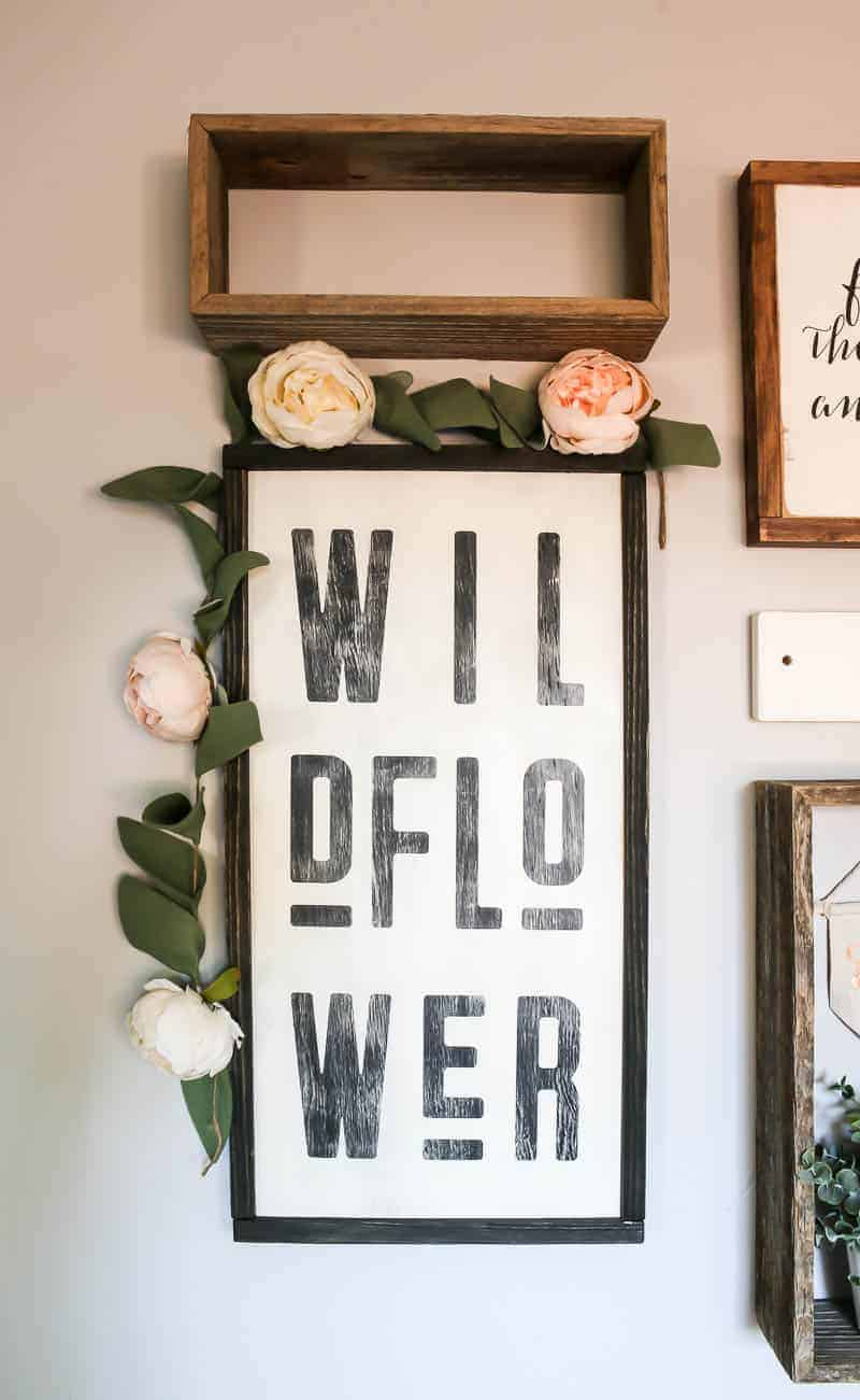 Wildflower wall art with black frame and faux flower garland hanging on corner