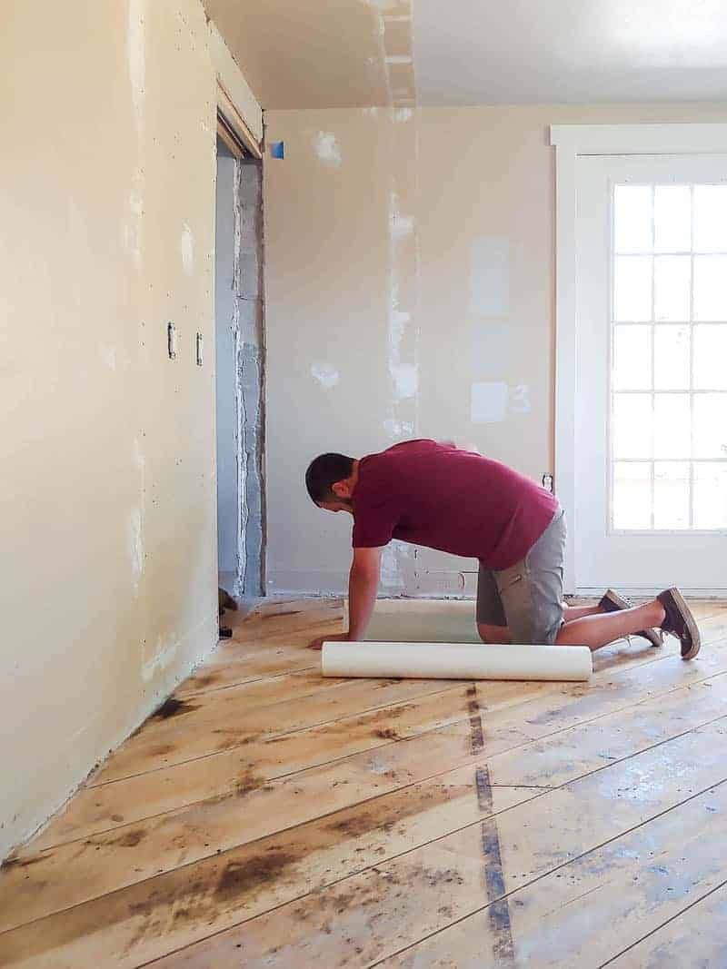 Man installing the vapor barrier to go underneath cheap hardwood flooring.
