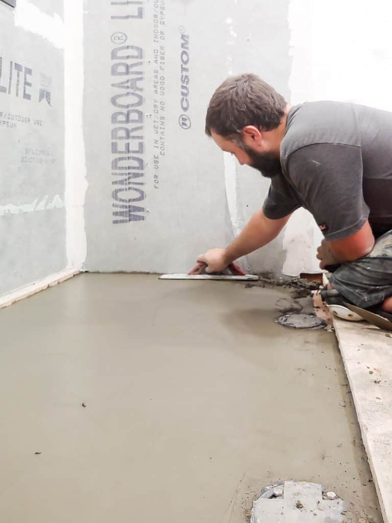 There is a man flattening cement to the floor to create a shower base.