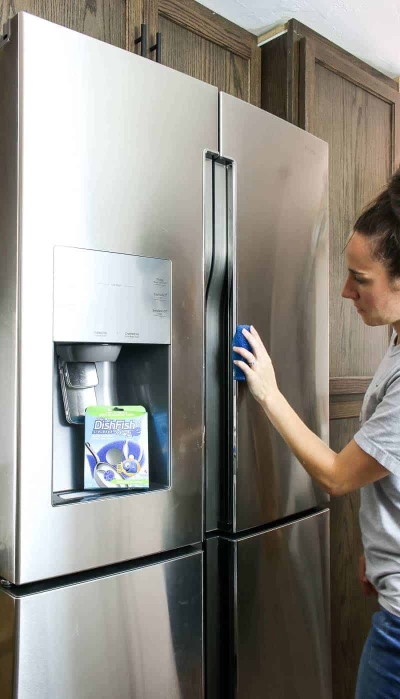 Wiping the front of the fridge to complete the deep refrigerator cleaning
