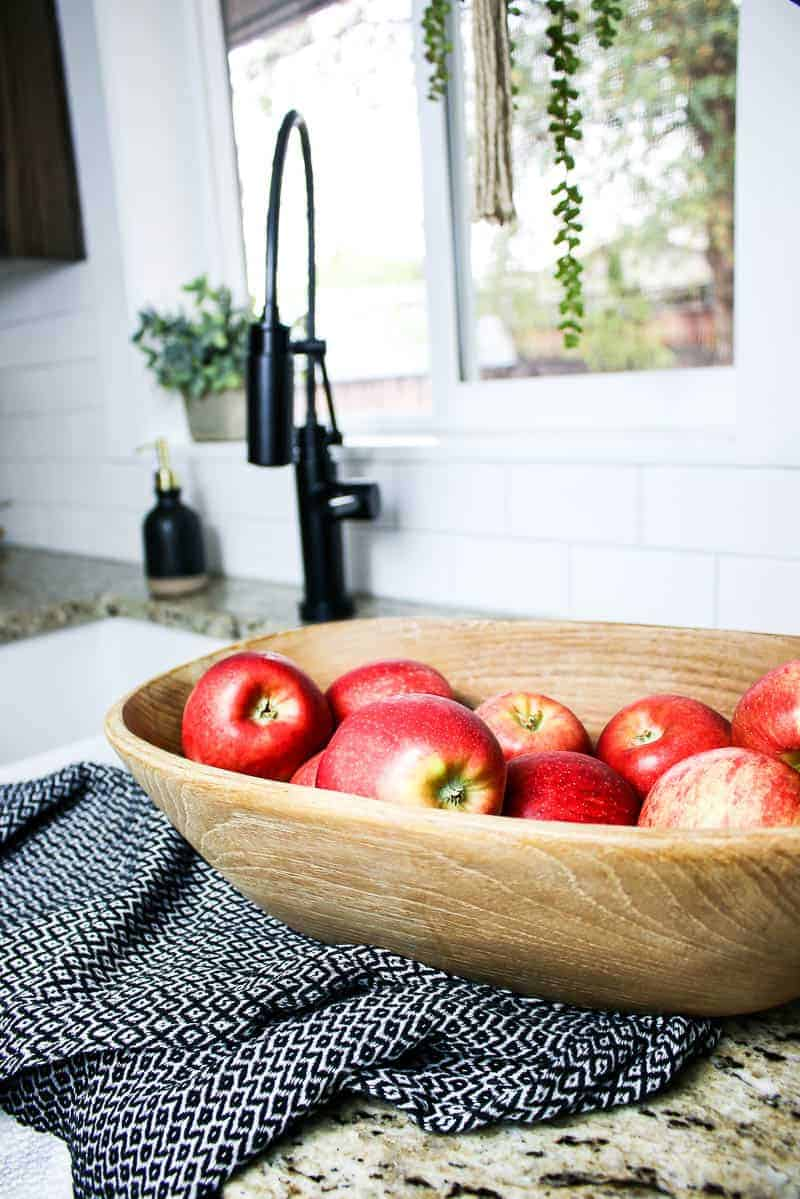 Wooden bowl with apples in front of the kitchen sink