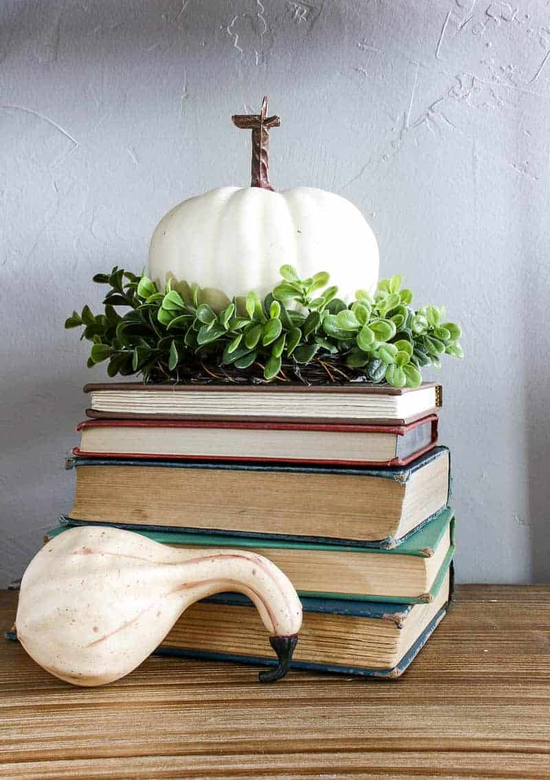 White pumpkin decorations for fall on top of the books.