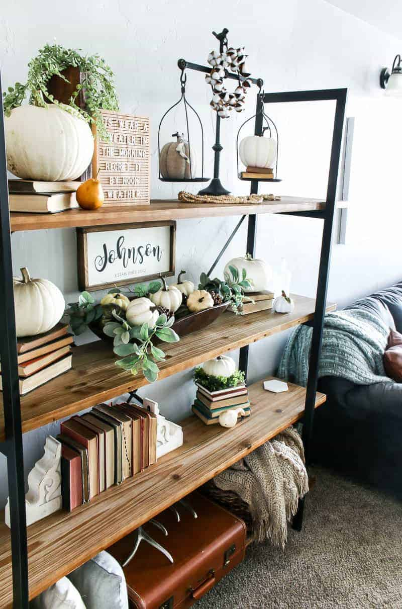 Side shot of the Living room shelf ideas containing pumpkin decorations on top of the farmhouse shelf decors.