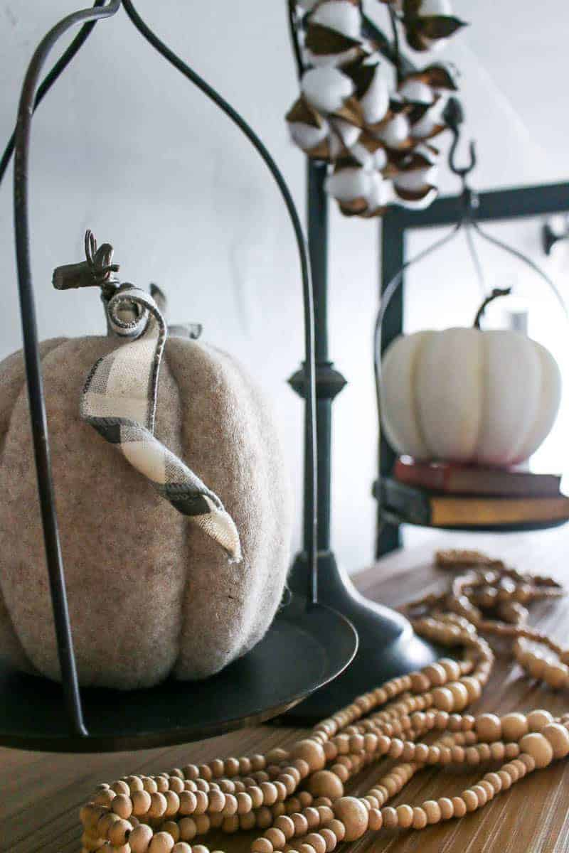 Close up photo of the mini white pumpkin decorations for fall on the vintage scale.