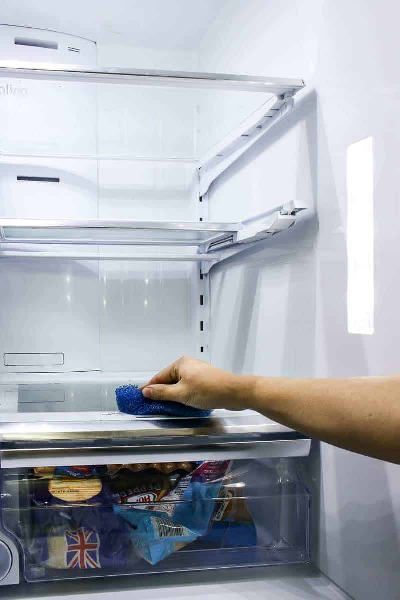 Refrigerator clean out by wiping out all the crumbs and mess off of the shelves