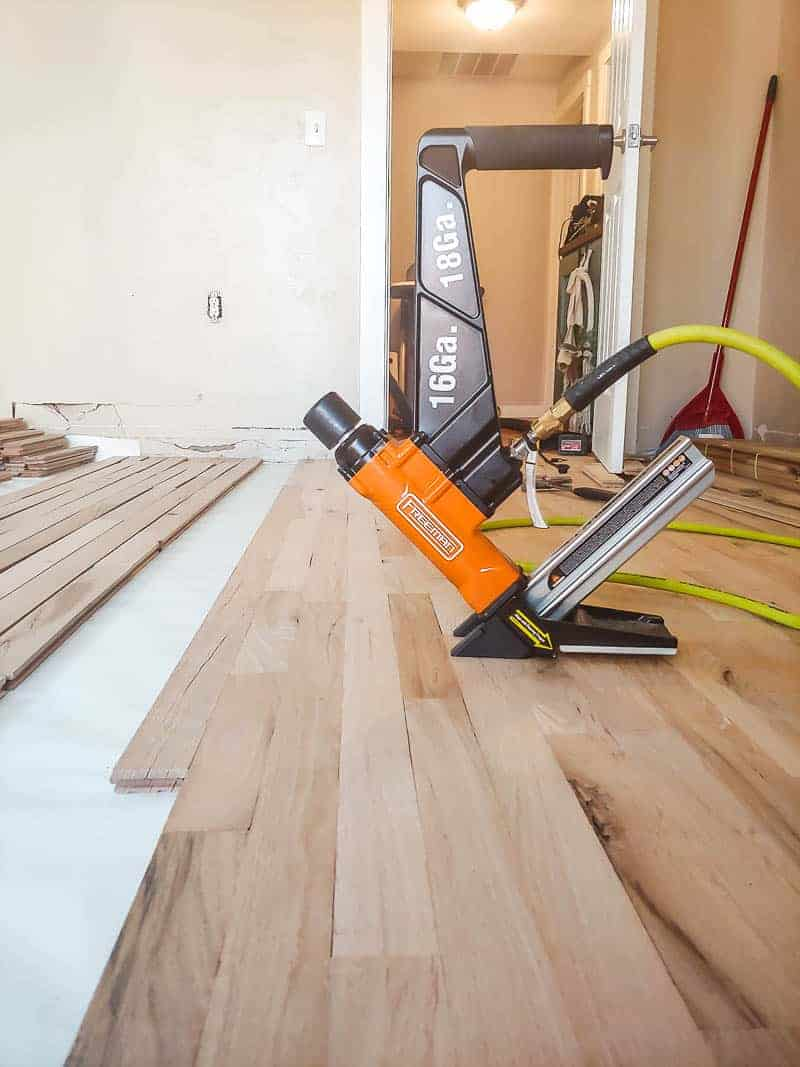 Flooring nailer laying on top of hardwood flooring in the middle of installing