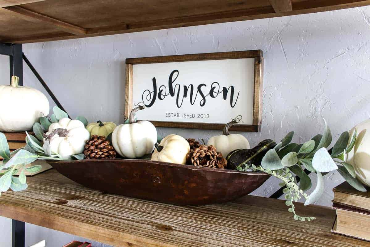 Wooden dough bowl holding all of the cute mini pumpkins, scented pinecones, some pieces of faux greenery and the personalized family sign.
