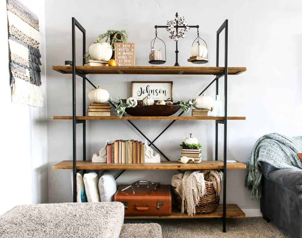 Living Room shelf ideas containing pumpkin decorations, books, wood signs, old suitcase, basket and pillows.