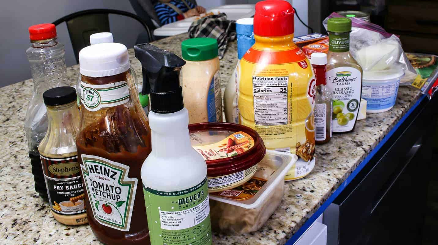 Food and sauces on the countertop taken out of the refrigerator during a fridge clean out