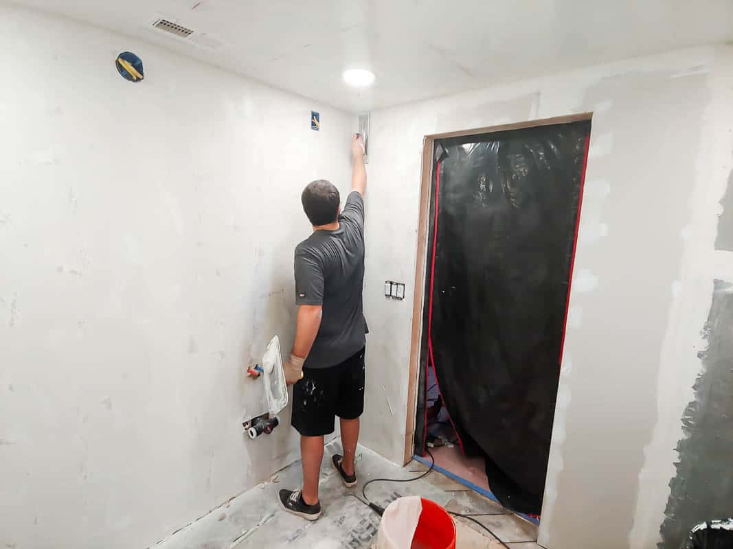 Man painting the walls with white paint.