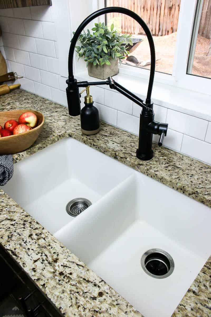 Closer view of the white undermount sink and black faucet.
