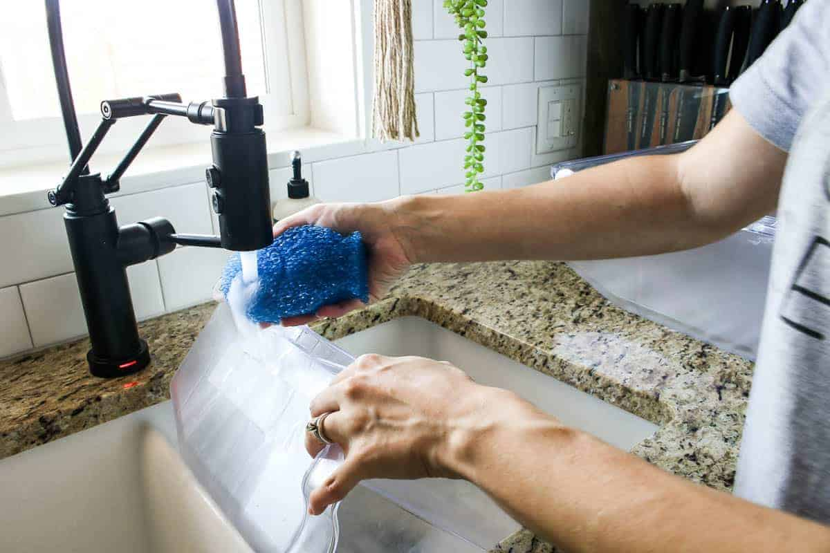 Washing the refrigerator drawers in the kitchen sink with the DishFish scrubber sponge