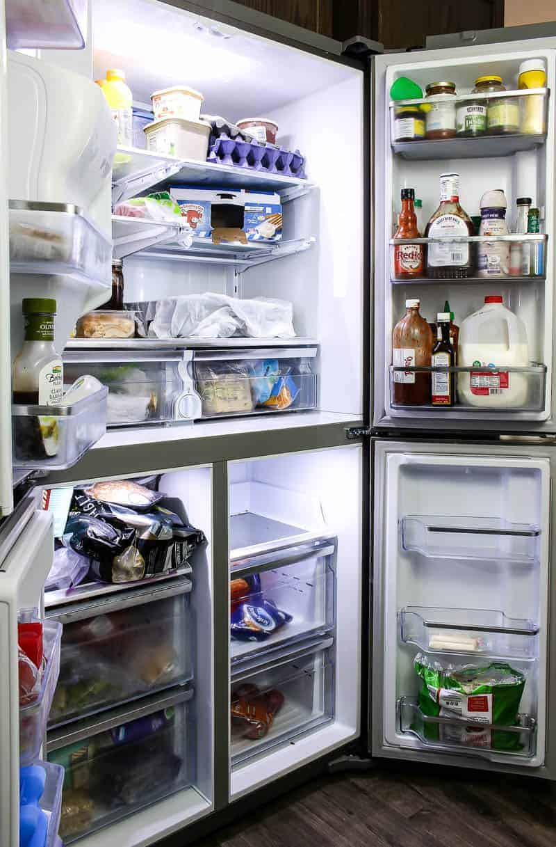 Opened refrigerator doors showing the entire shelves and the food inside