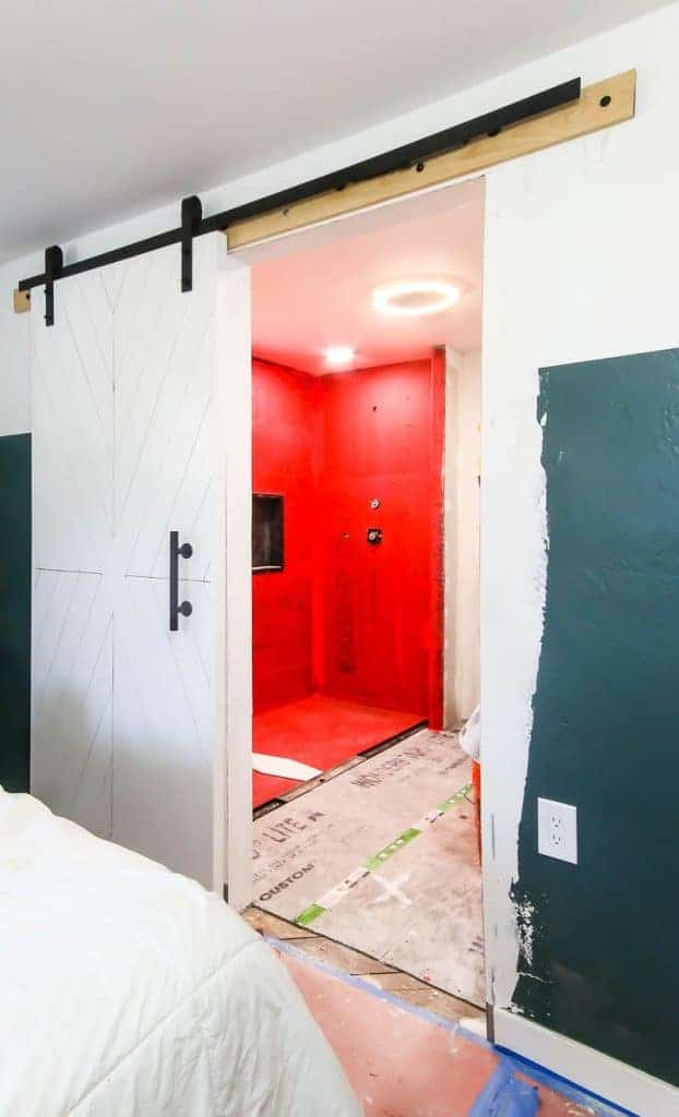 Shower is under construction, with red gaurd and plywood flooring. shot is taken from the bedroom.