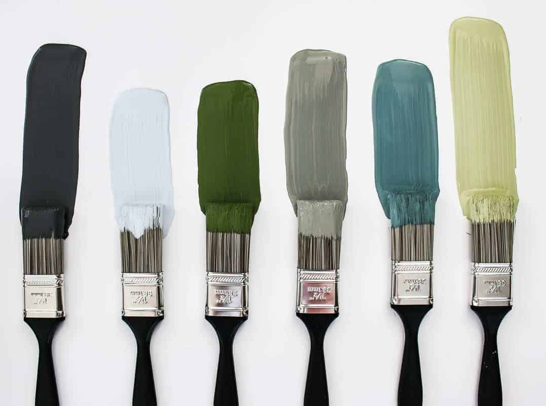 Nature inspired colored paint samples against a white background with paint brushes