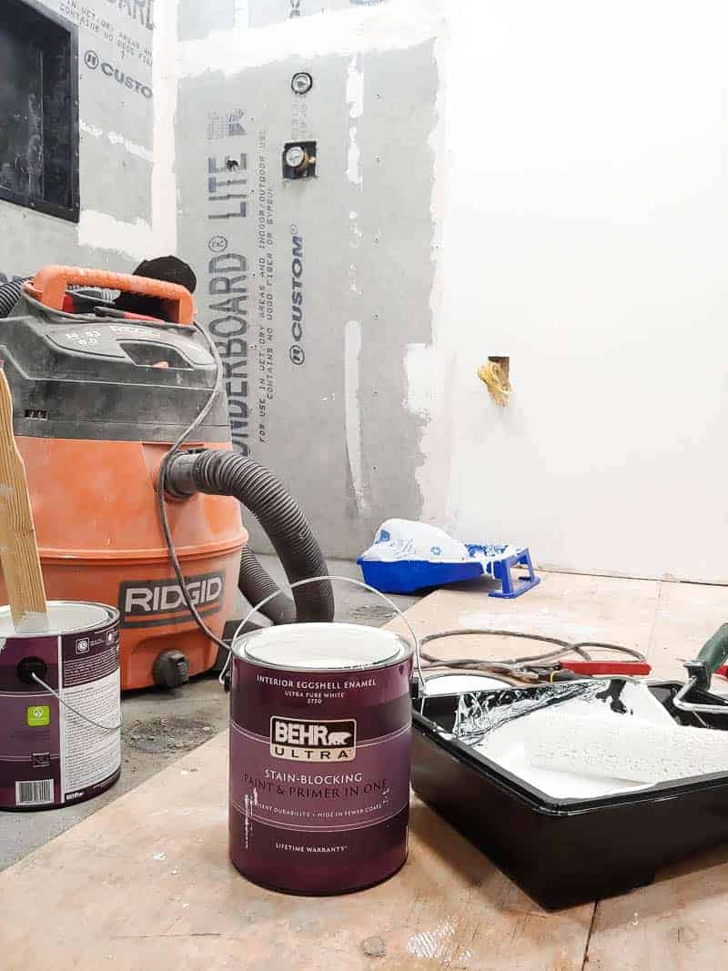 Can of Behr painting sitting on ground next to paint tray with shopvac in the background and concrete backer board up on the walls during a bathroom renovation