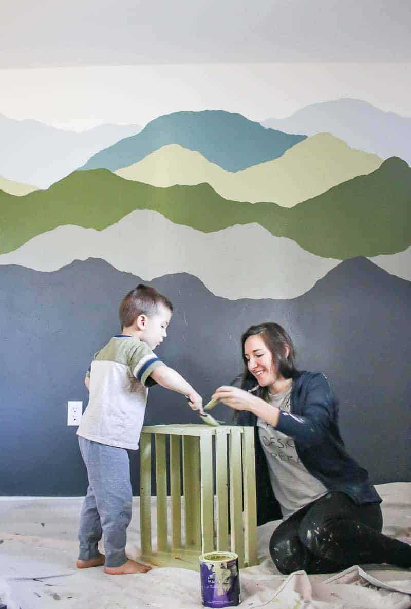 Painted wall behind the mother and son painting a wooden crate
