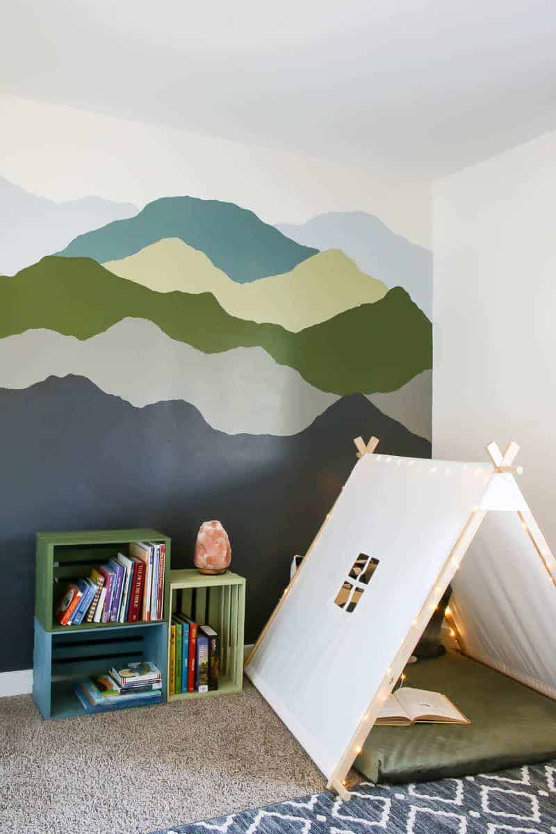 Mountain mural, colorful pallet bookshelves and toddler reading nook with teepee tent and dog bed for floor mat