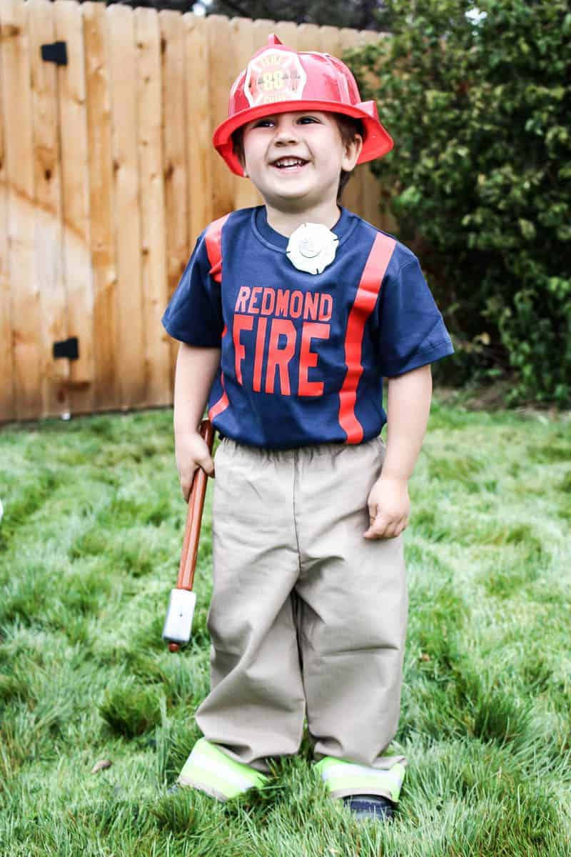 Toddler boy wearing personalized Halloween costume for fireman with hat, customized shirt, red suspenders, badge and firefighter pants