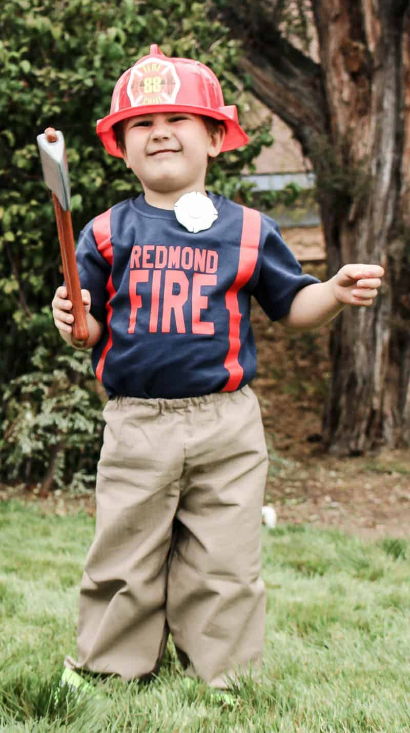 Toddler boy outside on grass wearing firefighter Halloween costume with hat, personalized shirt that says Redmond fire department with red suspenders, badge, plastic axe and firefighter pants with reflective tape