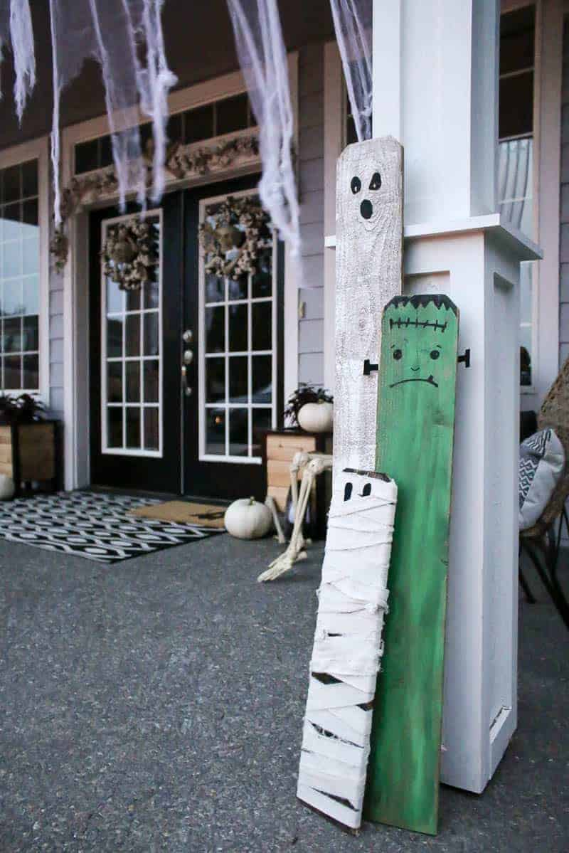 Upcycled halloween porch decorations made with fence boards painted into ghost, frankenstein and mummy to decorate the front porch for Halloween