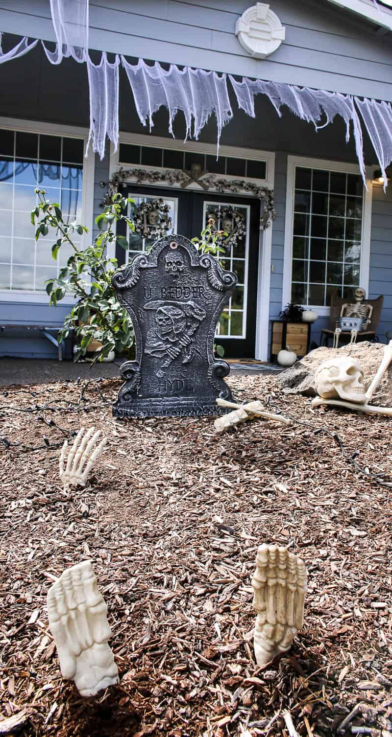 Fake gravestone on the front lawn, skeleton hands and feet with curtains in the porch roof as the Halloween Porch Decor
