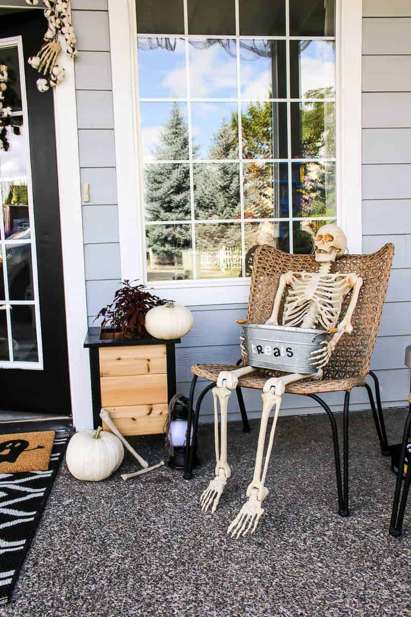 Halloween Porch Decor including pumpkins and full skeleton sitting on the porch chair.