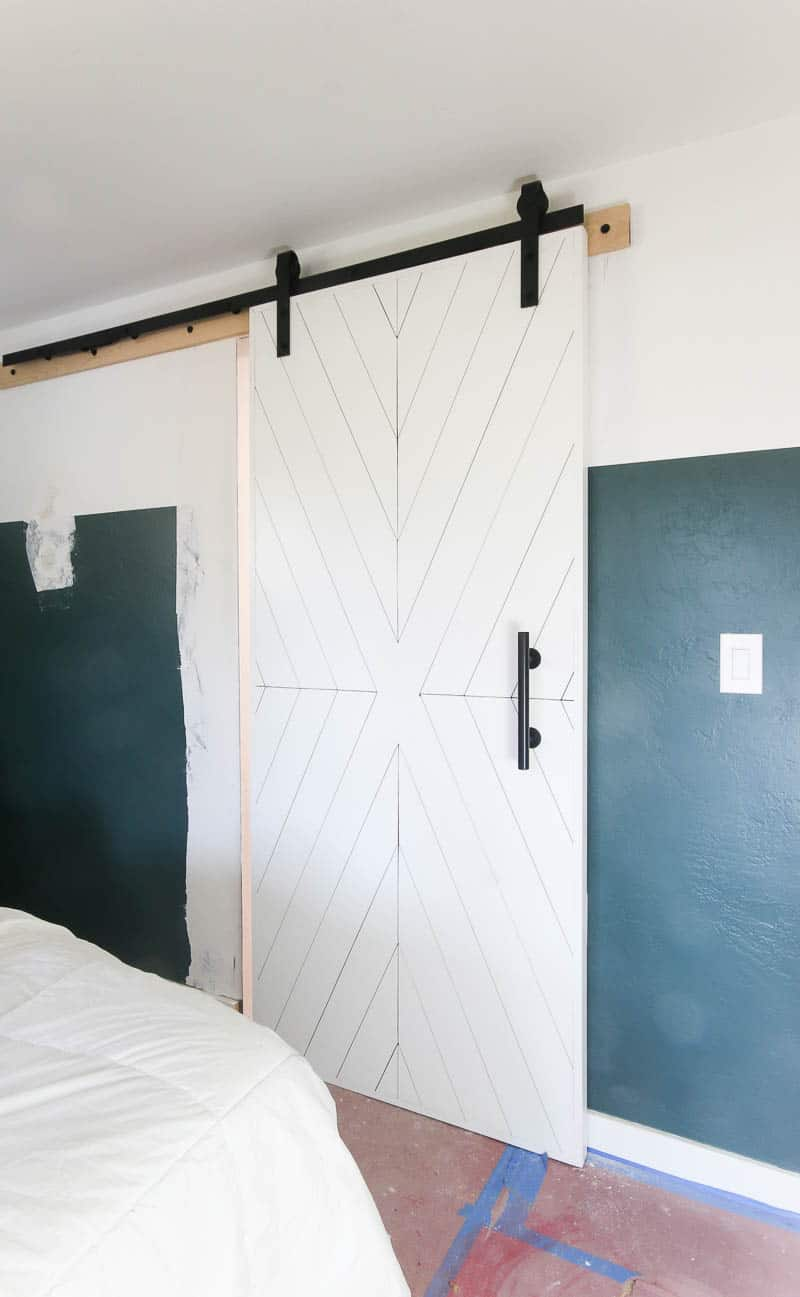 White sliding barn door with modern black hardware hanging in a bedroom with white and green two tone walls