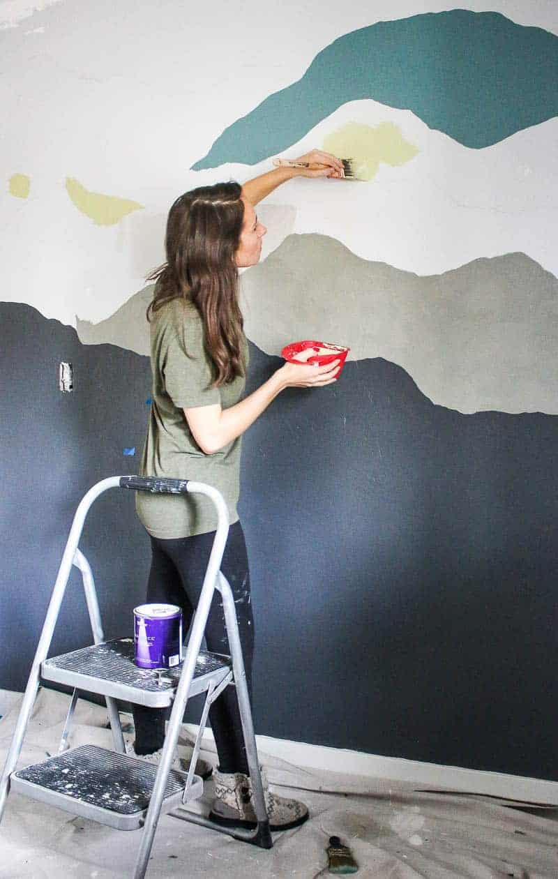 Full body shot of woman painting the fourth color of the mountain mural