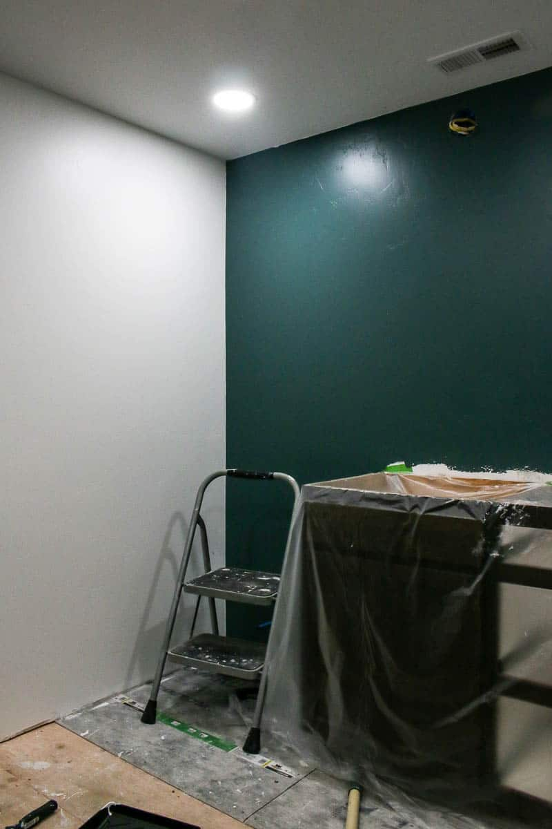 Dark green accent wall with Meteorological paint color on one wall during bathroom renovation