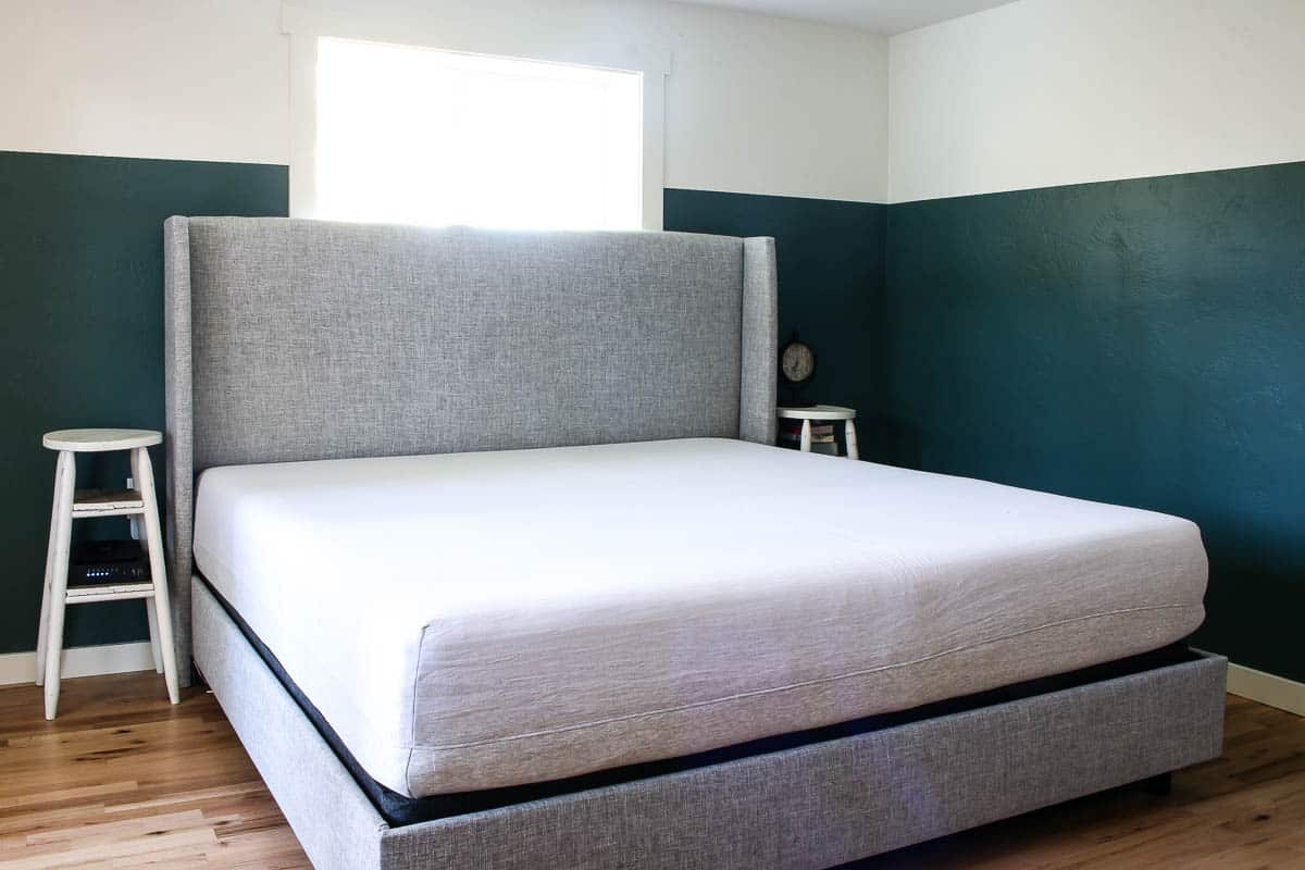 Two tone walls with green and white and gray upholstered bed with two DIY bed side tables made from barstools