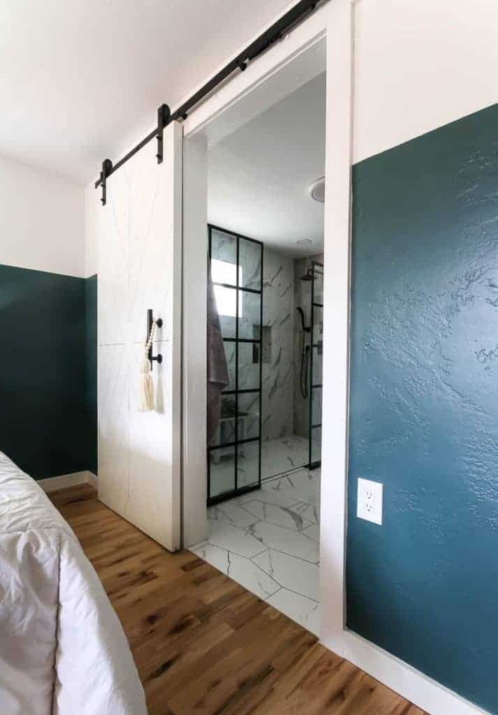 Modern barn door with x shaped design with blanks and black hardware looking into modern bathroom with marble tile and black shower doors