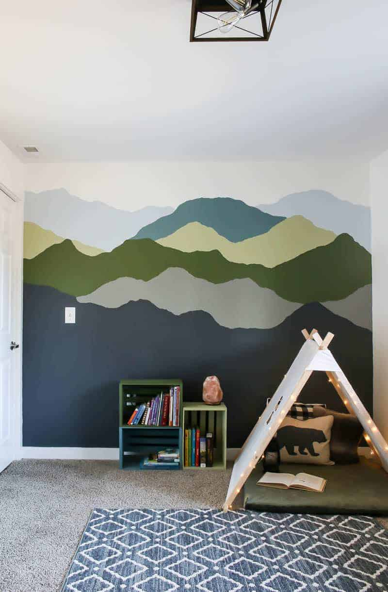 Full view of the mountain mural paint, colorful pallet bookshelves and cozy nook for the boys new room.