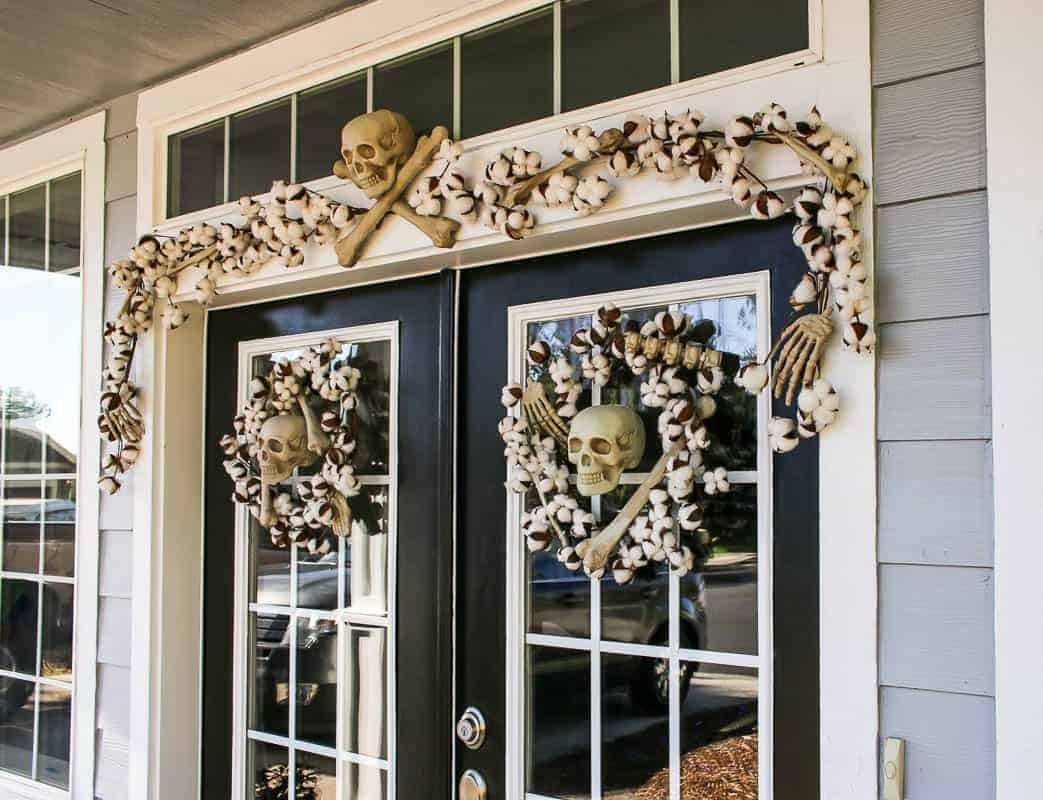 Two wreaths for each door with skulls and a garland on top of the front door.