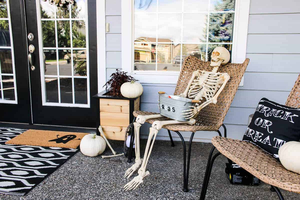 Skeleton holding the metal tub with treats sitting beside another chair with Trick or Treat throw pillow and pumpkins all over for the Halloween Porch Decor