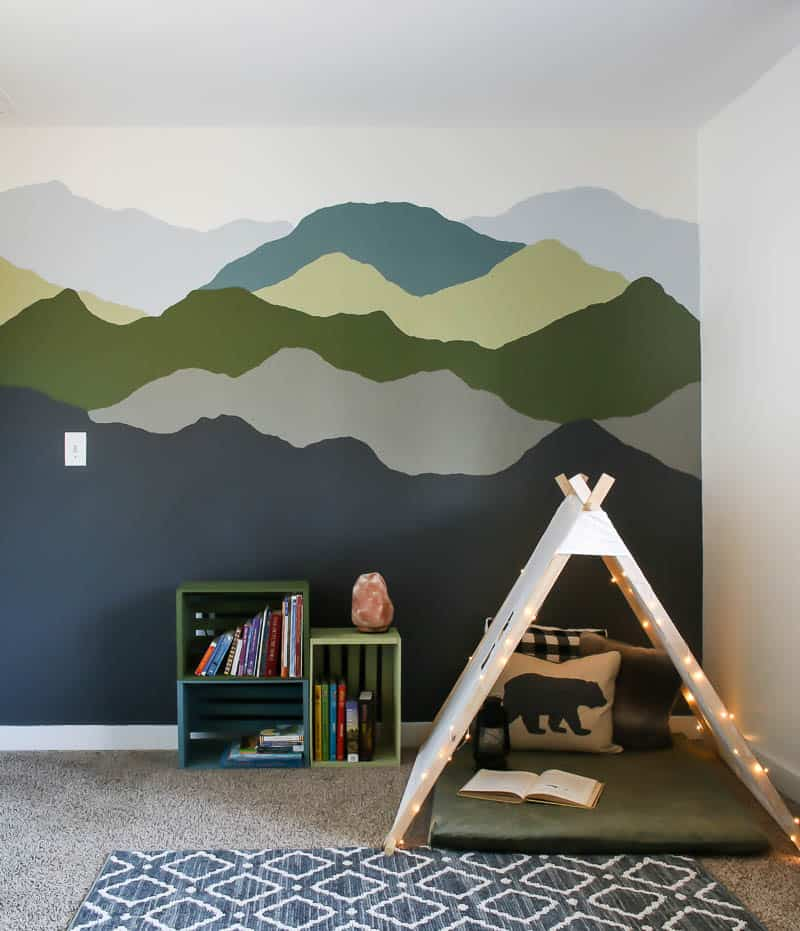 Behr Graphic Charcoal painted on bottom of mountain mural in kid's space with a nature inspired color palette
