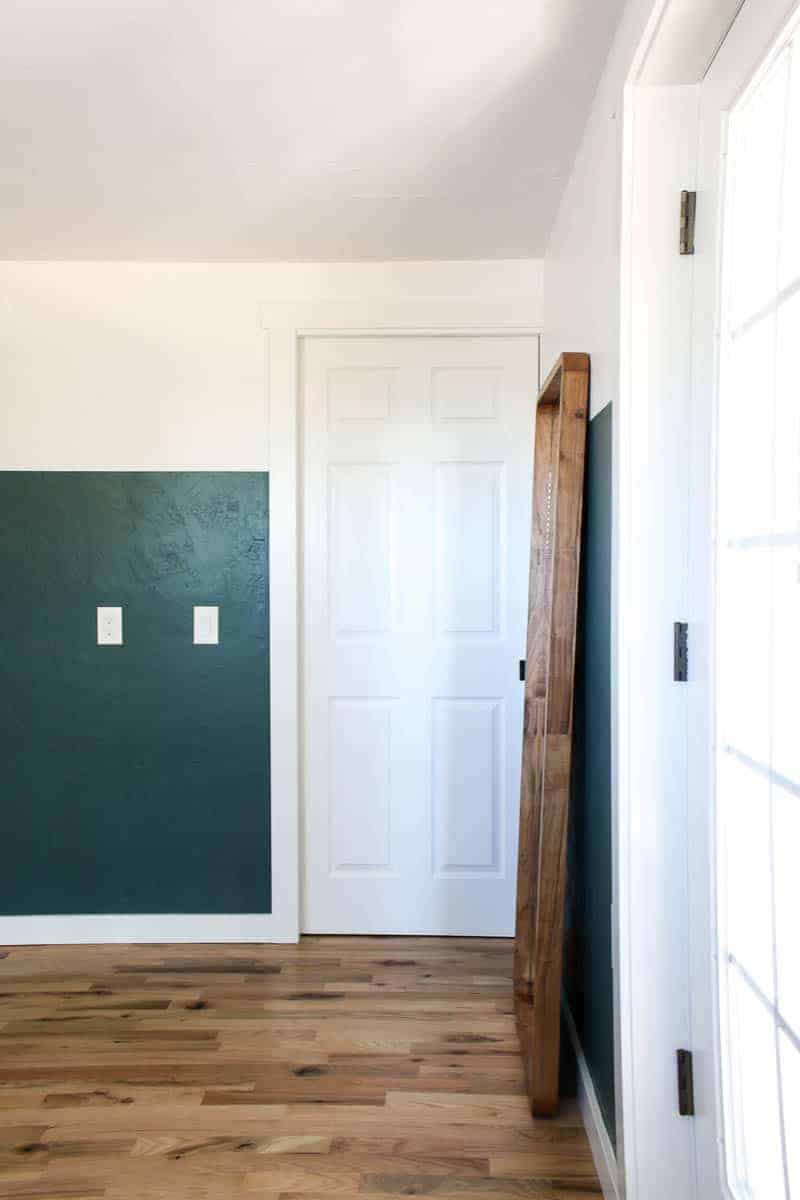 bedroom two tone walls with white pocket door leading to closet, new hardwood floorings and wood full length leaner mirror