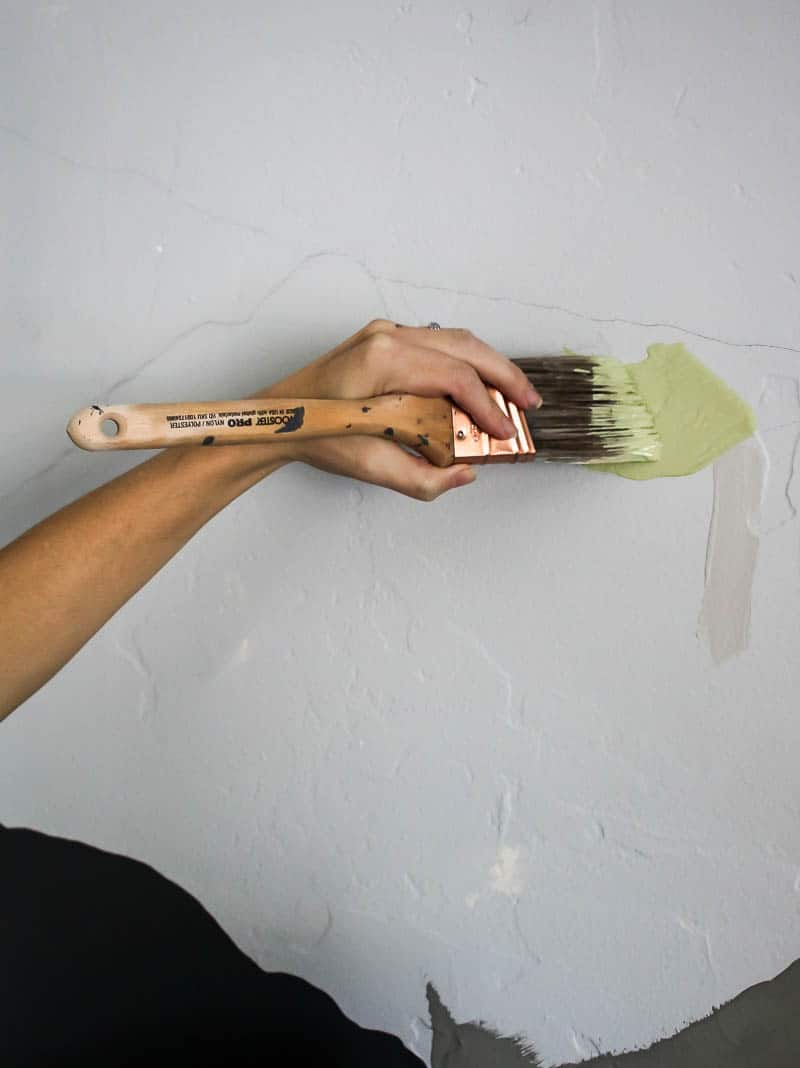 Painting a small section of the mountain mural with an angled paint brush