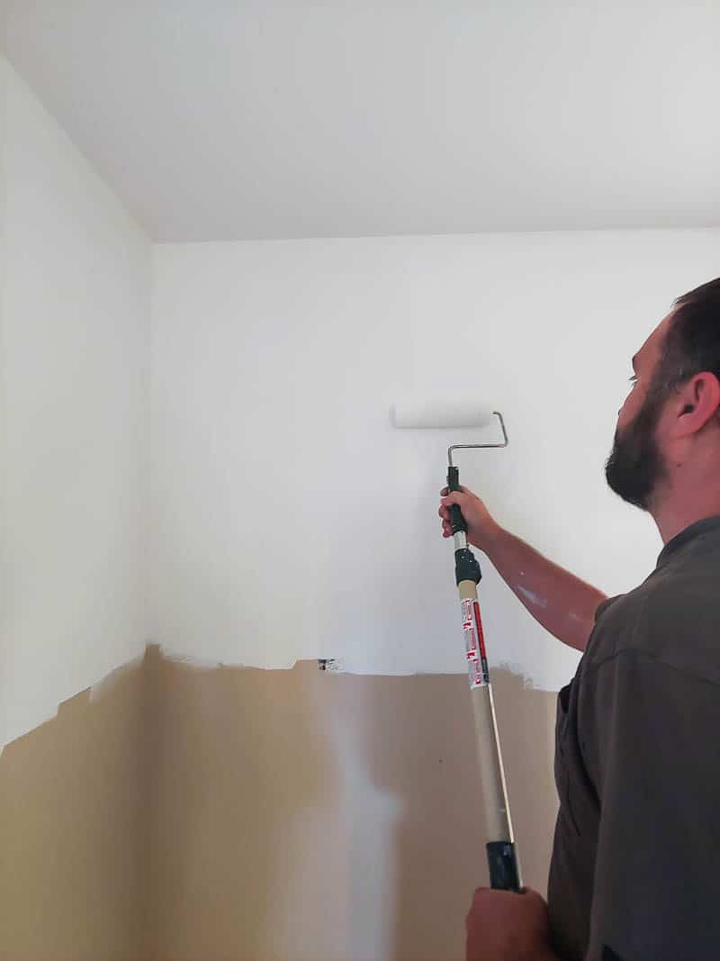 Ma adding the first coat of paint on the bedroom wall