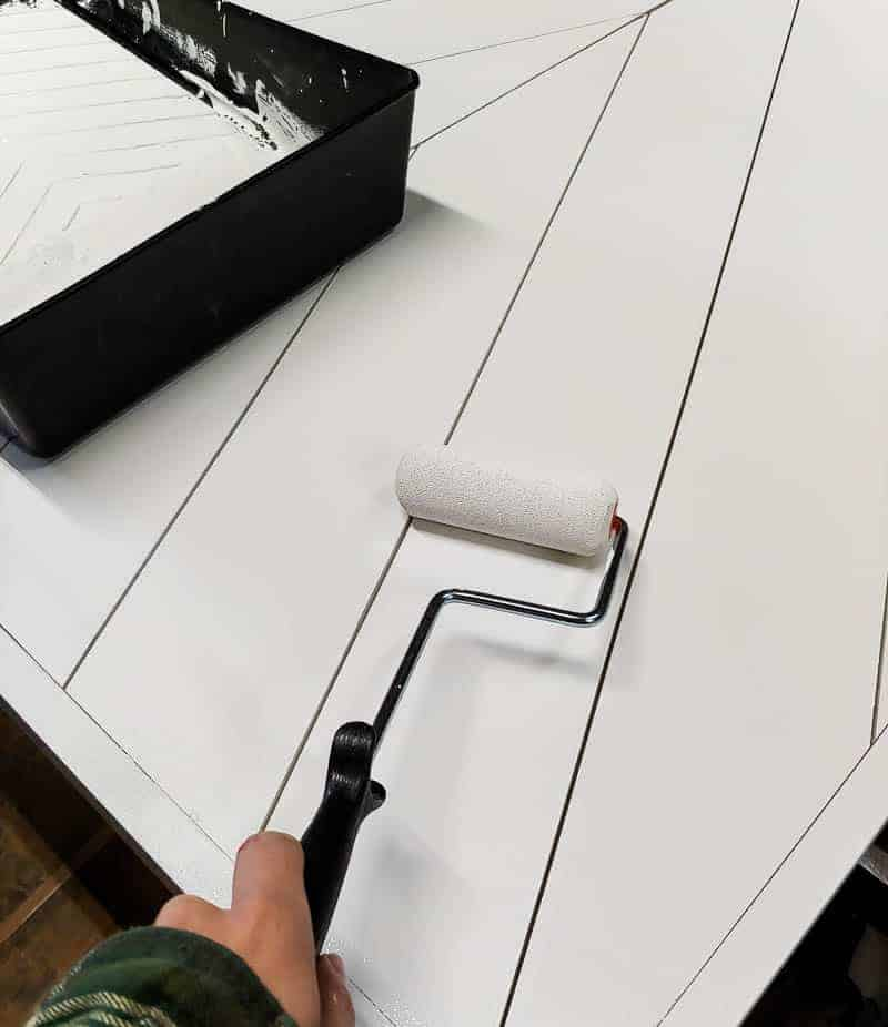 Painting the barn door with white paint using a roller for tutorial on how to build a barn door